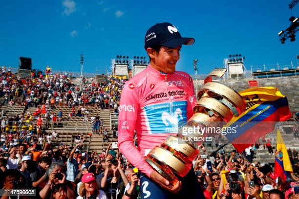Overall race winner Team Movistar rider Ecuador's Richard Carapaz holds the Never ending trophy during podium ceremonies in the Verona arena after...