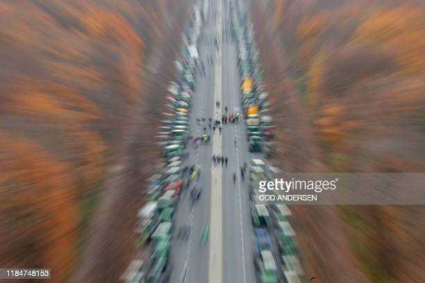 Overall view and zoom effect on hundreds of farmers lining up with their tractors along Strasse des 17 Juni Avenue towards Brandenburg Gate during a...