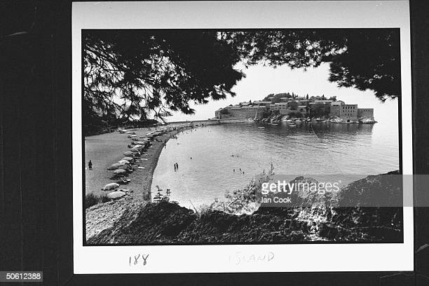 Overall view of the picturesque island of Sveti Stefan on the Adriatic w clean sweeping beach lined w large umbrellas on the Adriatic where former...