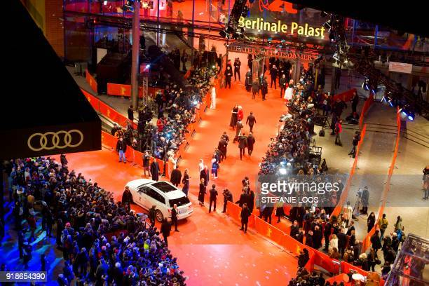 Overall view shows guests and stars arriving on the red carpet for the opening ceremony of the 68th Berlinale film festival with the premiere of Isle...