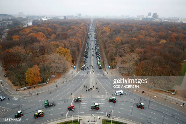 """Overall view shows hundreds of farmers lining up with their tractors along """"Strasse des 17. Juni"""" Avenue towards Brandenburg Gate during a protest on..."""