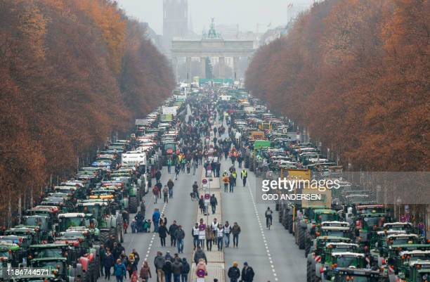 Overall view shows hundreds of farmers lining up with their tractors along Strasse des 17 Juni Avenue towards Brandenburg Gate during a protest on...
