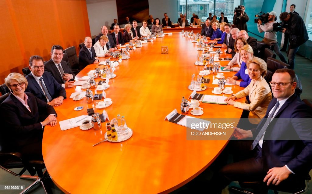 Overall view shows the new cabinet members sitting around the table at the start of the first new cabinet meeting lead by German Chancellor Angela Merkel (5thL) at the chancellery in Berlin on March 14, 2018. German Chancellor Angela Merkel, bruised by half a year of post-election coalition haggling, was Wednesday narrowly confirmed by parliament to her fourth and likely final term at the helm of Europe's biggest economy. / AFP PHOTO / Odd ANDERSEN