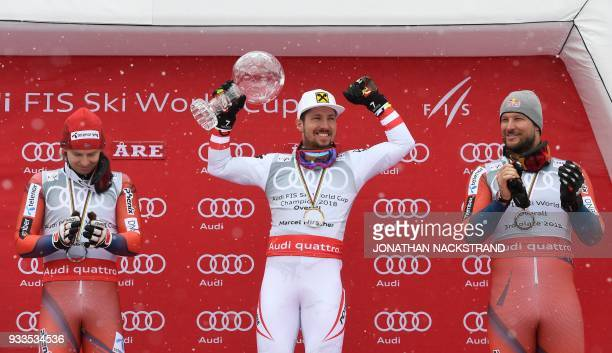 Overall winners of the Men's Alpine Skiing World Cup celebrate on the podium Henrik Kristoffersen of Norway Marcel Hirscher of Austria and Aksel Lund...