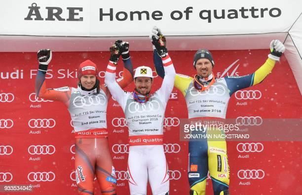 Overall winners of the Men's Slalom discipline of the Alpine Skiing World Cup pose on the podium Henrik Kristoffersen of Norway Marcel Hirscher of...