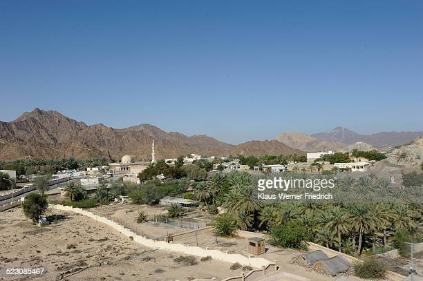 Overblick of the oasis and Arab enclave of Hatta with a mosque and palm trees, with the Hajar Mountains on the horizon, United Arab Emirates, Arabian Peninsula, Middle East, Asia