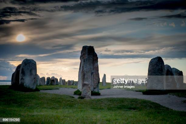 Overcast sky above standing stones at sunset