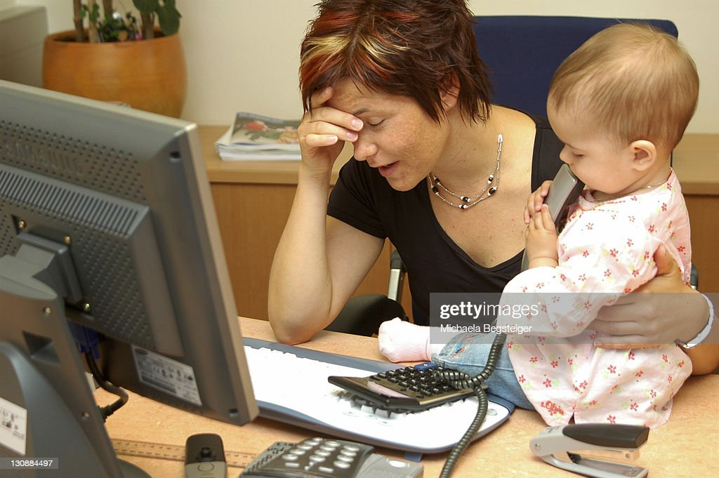Overcharged, working mother with child in office : Stock Photo
