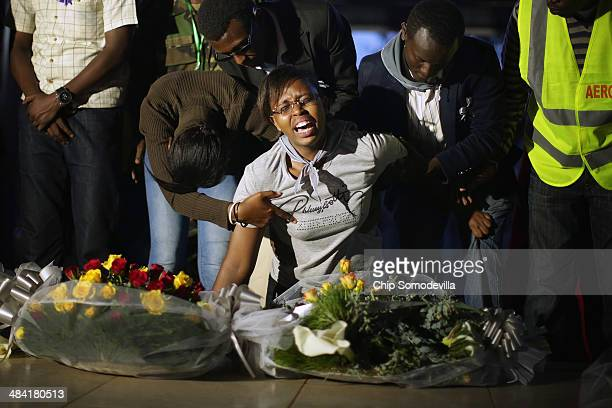 Overcome with grief a woman screams 'Mon pre' while kneeling next to one of the mass graves at the NyanzaKicukiro genocide memorial 20 years after...