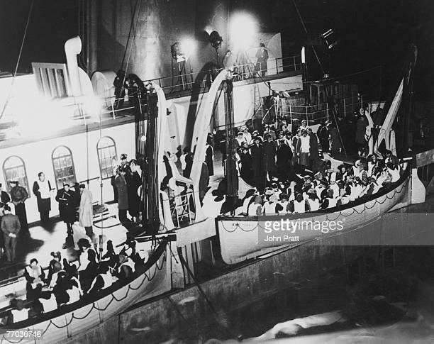 Overcrowded lifeboats are lowered from the stricken Titanic in a scene from Roy Ward Baker's 1958 film 'A Night To Remember', based on the sinking of...
