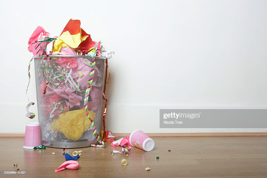 Overflowing bin filled with wrapping paper, party streamers, cups and balloons on wooden floor : Stock Photo