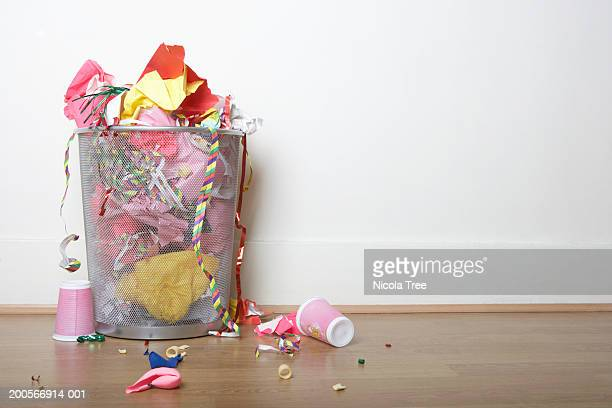 overflowing bin filled with wrapping paper, party streamers, cups and balloons on wooden floor - after party stock pictures, royalty-free photos & images