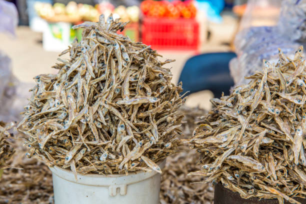 Overflowing bowls of dried fish at an outdoor market