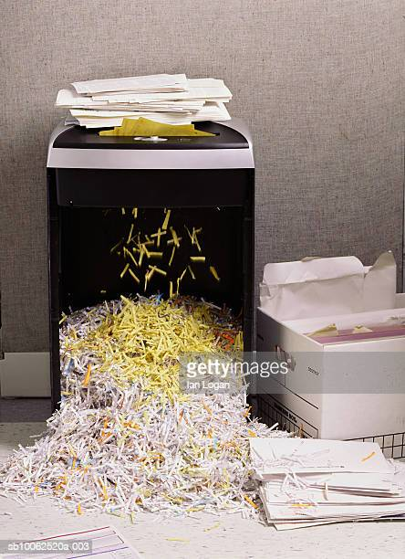 Overflowing paper shredder next to box of paper