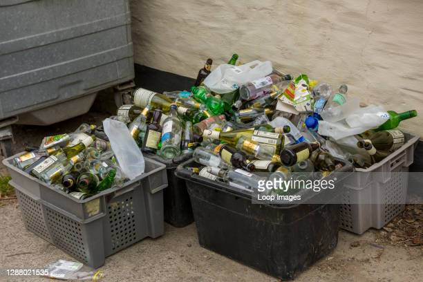 Overflowing recycling boxes containing plastic and glass bottles.