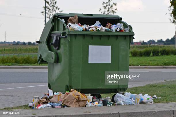 overflowing rubbish container on the street - garbage bin stock pictures, royalty-free photos & images