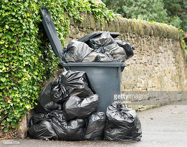 overflowing wheelie bin - garbage can stock photos and pictures