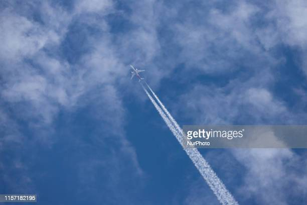 Overfly of an airplane of Asiana Airlines /OZ / AAR and type Boeing 777200ER in the summer blue sky with clouds The overflying Boeing 777 is a long...