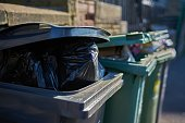 Overfull garbage cans wheelie bins close up