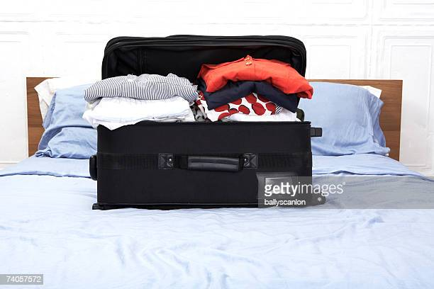 Overfull suitcase on bed