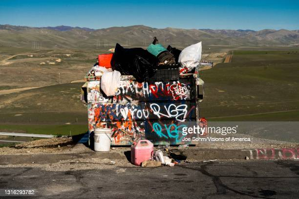 Overfull trash bend in central California is stuffed with garbage and bags of trash.