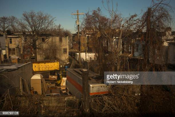 Overgrown back yards are seen in a partly abandoned neighborhood along the Amtrak railroad tracks January 9 2018 in Baltimore Maryland Often named...