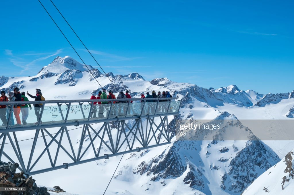 Overhanging viewpoint on the Tiefenbachkogl with people enjoying the view in the Sölden Ötztal ski area during a sunny winter day : Stock Photo
