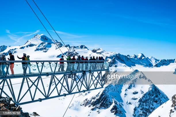 """overhangend uitkijkpunt over de tiefenbachkogl met mensen die tijdens een zonnige winterdag genieten van het uitzicht in het skigebied sölden ötztal - """"sjoerd van der wal"""" or """"sjo"""" stockfoto's en -beelden"""