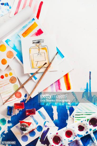 Overhead artist workplace with watercolor, palettes and swatches