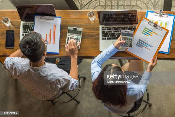Overhead Business Angles: Business people calculating numbers on sales report