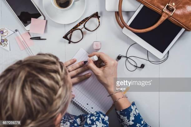 Mujer de negocios ángulos arriba en oficina escritorio pintura uñas