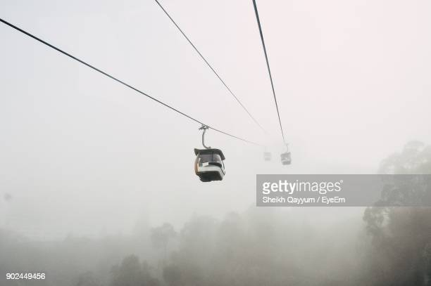 overhead cable car against sky during foggy weather - overhead cable car stock pictures, royalty-free photos & images