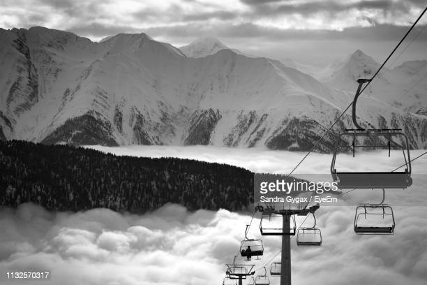 overhead cable car against snow covered mountains and sky - sandra gygax stock-fotos und bilder