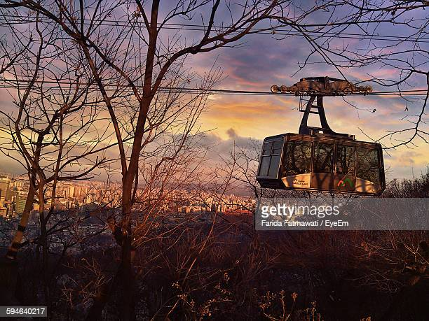 Overhead Cable Car Over Bare Trees Against Cloudy Sky During Sunset