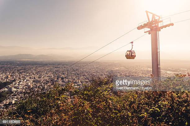 Overhead Cable Car Over City Against Sky On Sunny Day