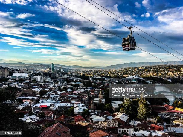 overhead cable car over city against sky - トビリシ ストックフォトと画像