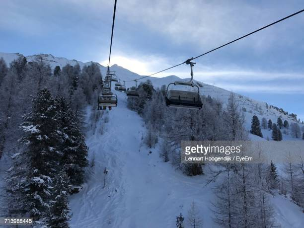 Overhead Cable Car Over Snow Covered Mountains Against Sky