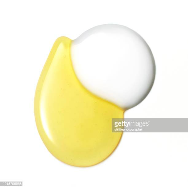 overhead close up view of cream and oil merging, isolated on a white surface - óleo essencial imagens e fotografias de stock