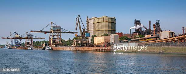 Overhead cranes and barges docked at the steelworks of ArcelorMittal world's largest steel producer port of Ghent East Flanders Belgium