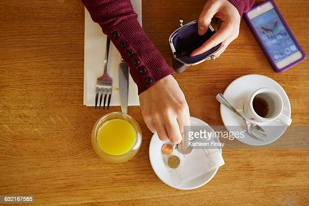 Overhead cropped view of woman leaving gratuity in restaurant