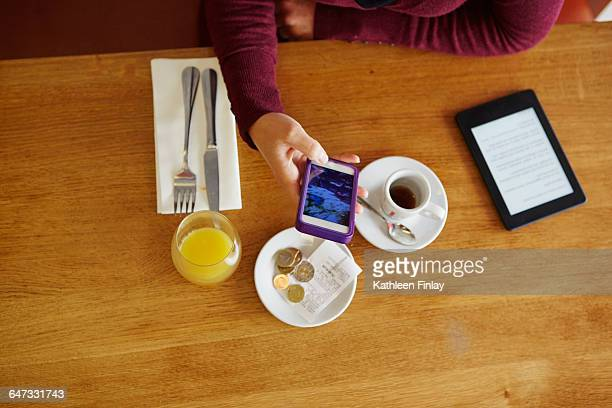 Overhead cropped view of woman reading smartphone text in restaurant