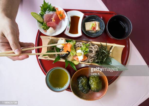 overhead first person view of hand on  japanese food on a tray with sashimi, soba noodles and green tea. - 蕎麦 ストックフォトと画像