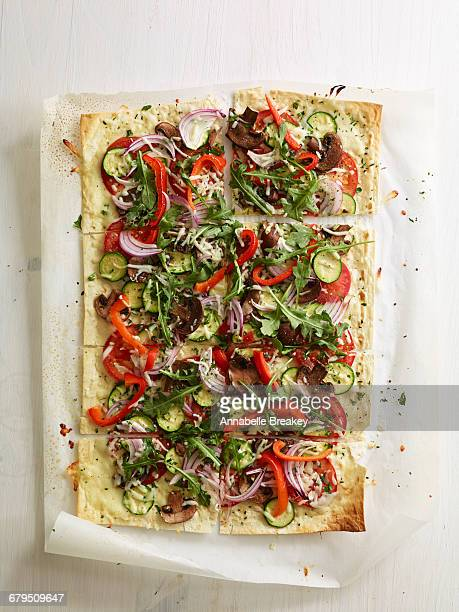 Overhead flat bread vegetable pizza on parchment