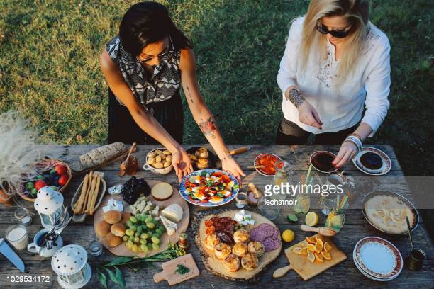 overhead image of two young women preparing food for picnic in the nature - tapas stock photos and pictures