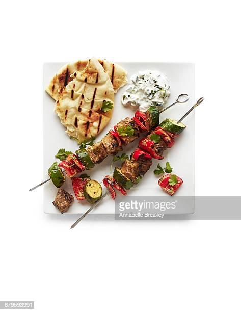 Overhead of beef kebabs with tzatziki & pita bread
