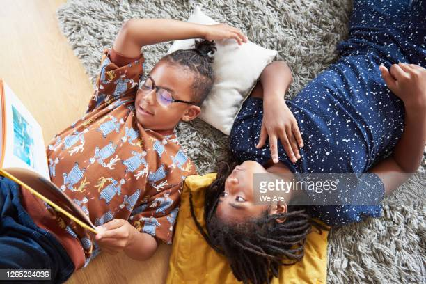 overhead of brothers reading while lying on floor - sibling stock pictures, royalty-free photos & images