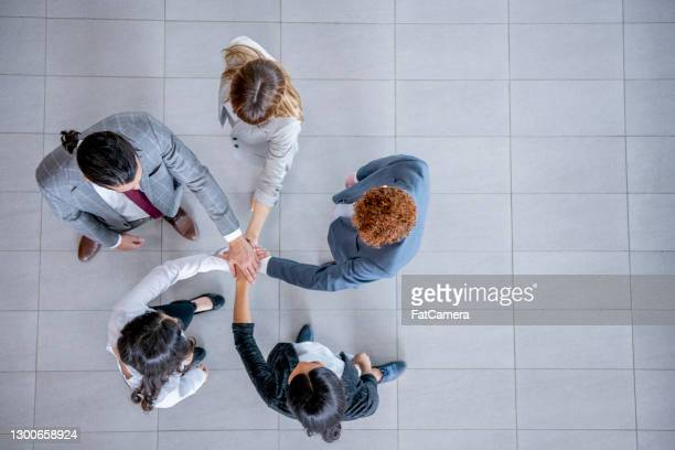 overhead of business people making a pact together - hands clasped stock pictures, royalty-free photos & images