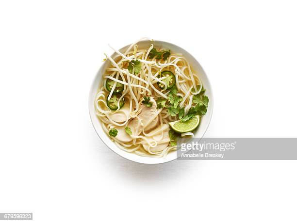 Overhead of chicken pho in white bowl on white