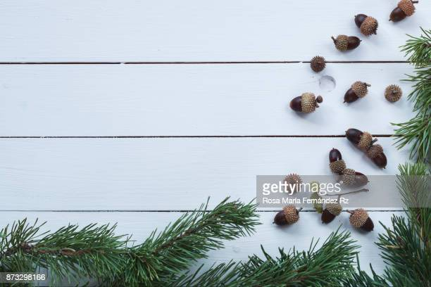 Overhead of Christmas frame with fir tree and acorn on pink painted wooden background. Copy space.