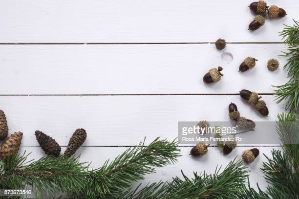 overhead of christmas frame with fir tree, pine cone and acorn on painted wooden background. copy space. - holiday background stock photos and pictures